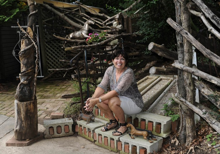 Artist Sherrill Cooper, who has made sculptures and decorations from found objects for her garden, sits on steps in a garden path. (Barbara Haddock Taylor/Baltimore Sun)