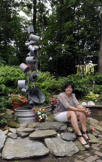 Artist Sherrill Cooper, who has made sculptures and decorations from found objects, sits with her most complicated creation, which is a fountain made of watering cans. (Barbara Haddock Taylor/Baltimore Sun)