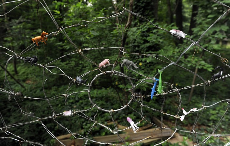 This is a spider web made from discarded coat hangers and plastic animals. (Barbara Haddock Taylor/Baltimore Sun)