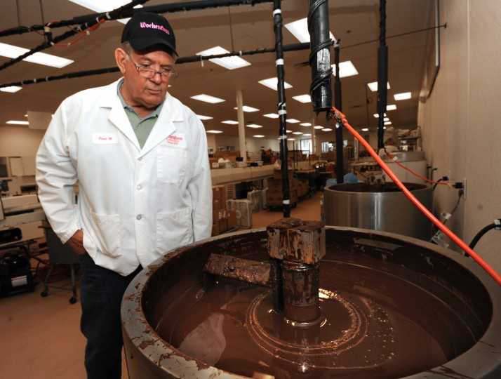 Paul Wockenfuss, owner and president of Wockenfuss Candies, is pictured next to a vat of chocolate that is constantly stirred by a mechanical arm to prevent clumping. (Algerina Perna/Baltimore Sun)