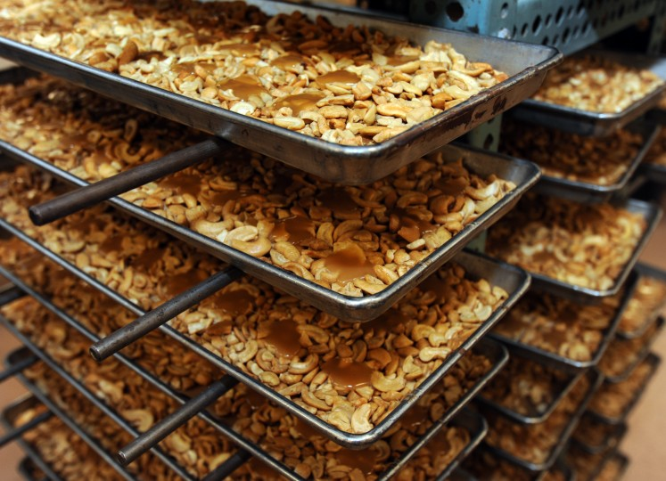 Trays stacked with caramel-covered cashews await the next step in the candy-making process: a coating of chocolate at Wockenfuss Candies on Harford Rd. (Algerina Perna/Baltimore Sun)