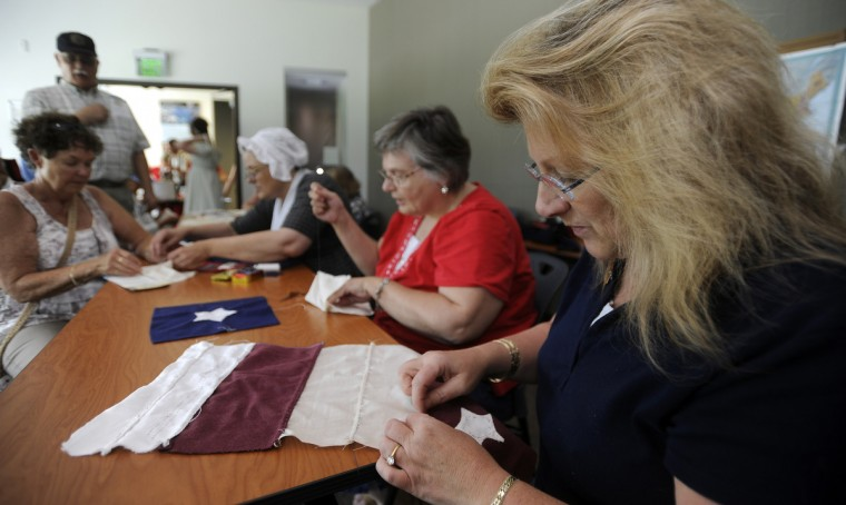 In the Fort McHenry visitors center, Karen Moss, right of Laytonsville, makes some practice stitches before sewing the real thing. She and other volunteers from the Maryland Historical Society are joined by members of the public and other volunteers as they start to sew a 30 X 40 foot replica of the 1813 version of the Stars and Stripes. It will be a replica of the one that was made by Mary Pickersgill. It will have 15 stars and 15 strips and is made of wool bunting that was made by an heirloom weaver. (Barbara Haddock Taylor/Baltimore Sun)