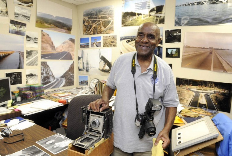 Timothy G. Hyman is standing at his desk with his original camera, left, which is a 1949 Speed Graphic (that still works) and wearing his current Nikon model, a D3100. (Barbara Haddock Taylor/Baltimore Sun)