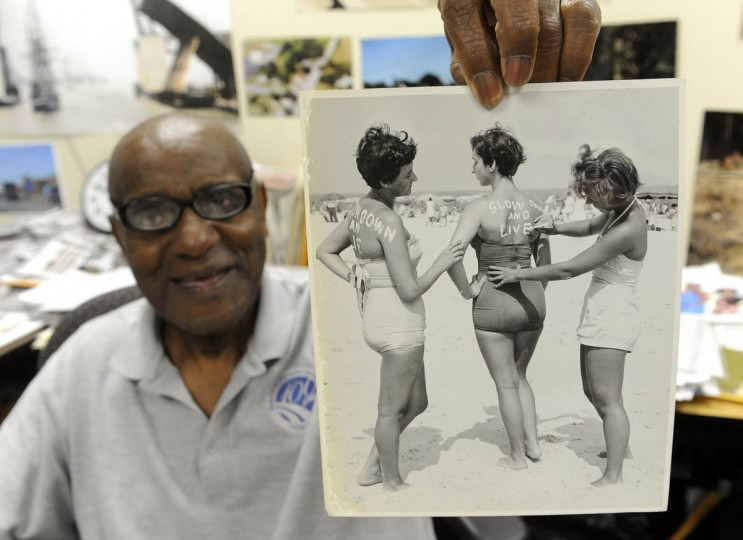 "Timothy G. Hyman, staff photographer for the Maryland State Highway Administration, holds one of his photographs from the 1960s. It shows three women on the beach at Ocean City, where there was a public awareness campaign about speeding that involved painting ""Slow Down and Live"" on the backs of women at the beach. (Barbara Haddock Taylor/Baltimore Sun)"