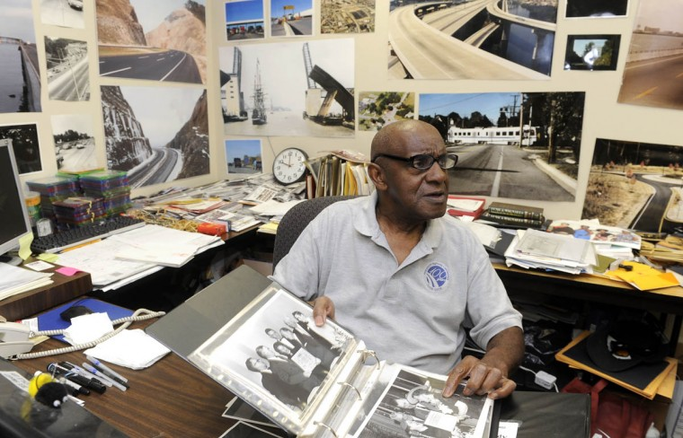 Timothy G. Hyman, staff photographer for the Maryland State Highway Administration, looks through a binder of photographs in his tiny office. The walls are lined with some of his pictures. (Barbara Haddock Taylor/Baltimore Sun)