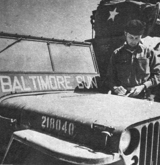 James M. Cannon, Sunpapers War Correspondent, uses the hood of his jeep as a desk in Korea. (Baltimore Sun)