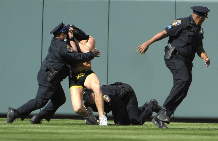 A fan dressed as Batman ran onto the field and eluded police for several minutes before being tackled during the Orioles game on April 6, 2012. (Gene Sweeney, Jr./Baltimore Sun)