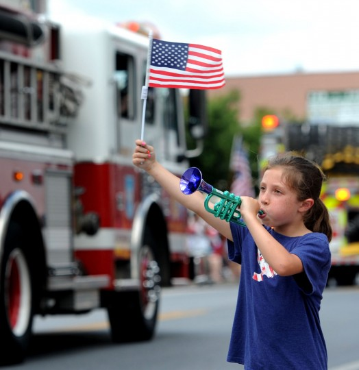 Sophia Taylor, 7, Eldersburg, waves a flag and blows a horn firefighters pass by in the Catonsville Fourth of July parade on Frederick Road. (Kim Hairston/Baltimore Sun)
