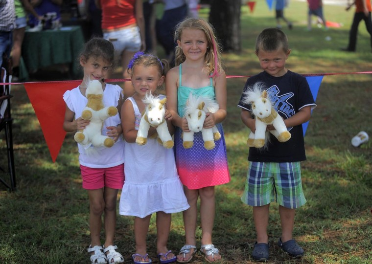 "Zoe Rosta, Olivia Shifler, Aliza Adams, and Parker Speiez of Cambridge, Maryland hold up their ""Misty"" stuffed animals. When the horses began to swim, all four children called out ""Misty!"" (Erin Kirkland/Baltimore Sun)"
