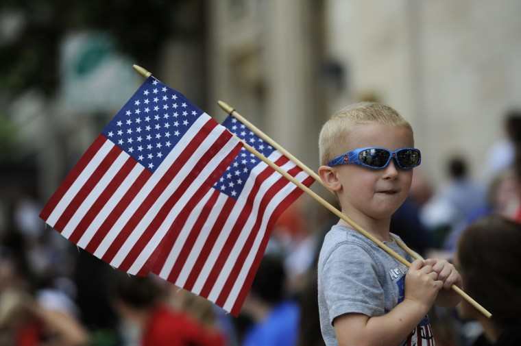 Brandon Armiger, 4 of Timonium, holds flags at the Towson Fourth of July parade. (Barbara Haddock Taylor/Baltimore Sun)