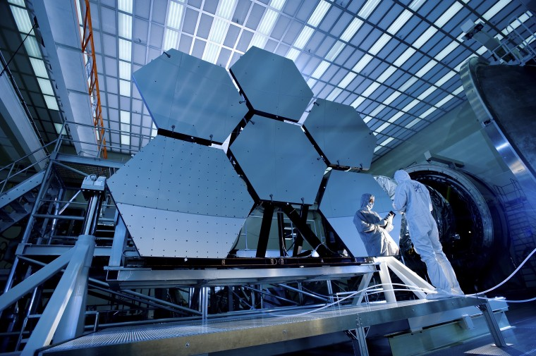 Jake Lewis of Ball Aerospace is reflected in a mirror array of the James Webb Telescope. (Courtesy of NASA/MSFC/David Higginbotham/Emmett Given)