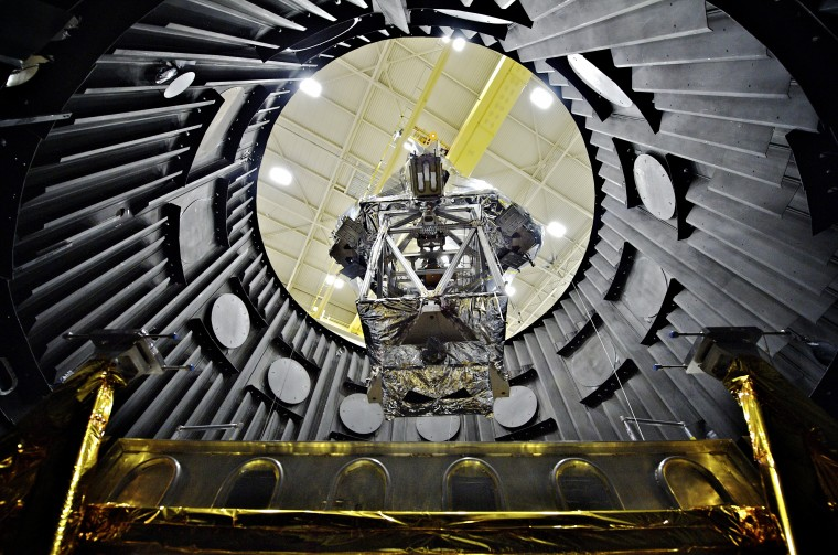 A crane lowers the Optical Telescope Element Simulator wrapped into a vacuum chamber to be tested to withstand the cold temperatures of space. (Courtesy of NASA Goddard/Chris Gunn)