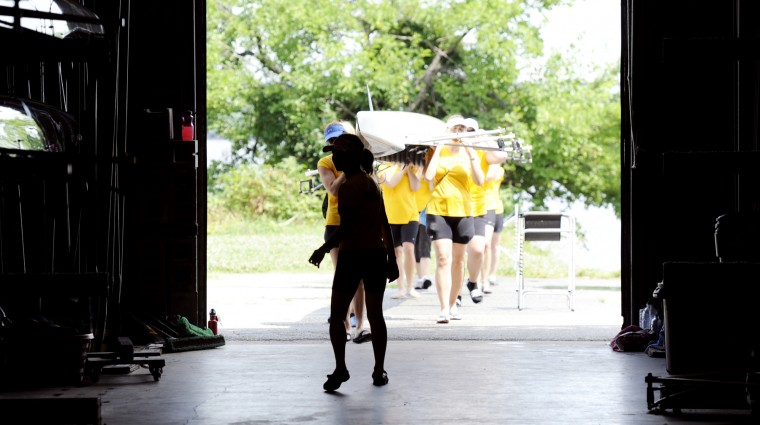 Coxswain Erica Mah, in shadow, leads her crew and the Federal Hill into the boathouse after practice. (Jon Sham/BSMG)