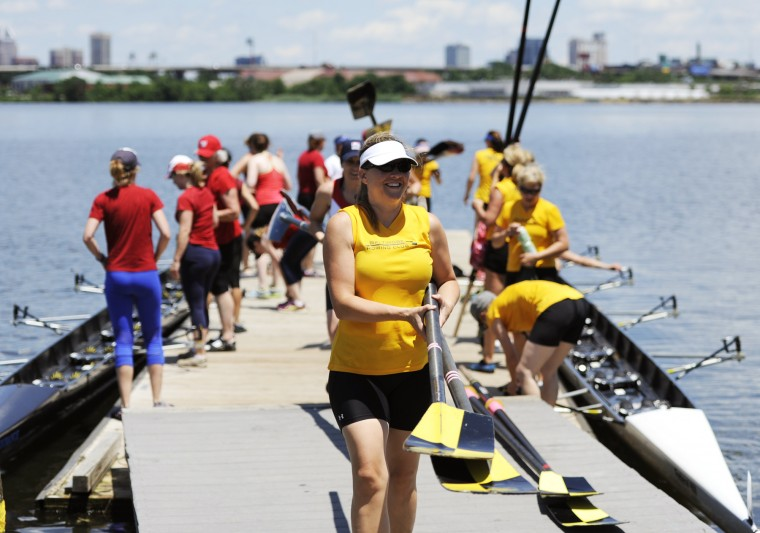 Kathleen Cummings, of the Row Like A Mother crew, carries a pair of oars up the docks after the race against Capital Rowing Club. (Jon Sham/BSMG)