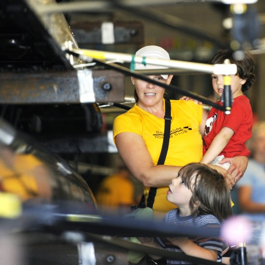 Rower Julie Baldi shows her two sons, Dario, 3, in her arms, and Giacomo Baldi, 5, the inside of the boat after their race on Saturday. (Jon Sham/BSMG)