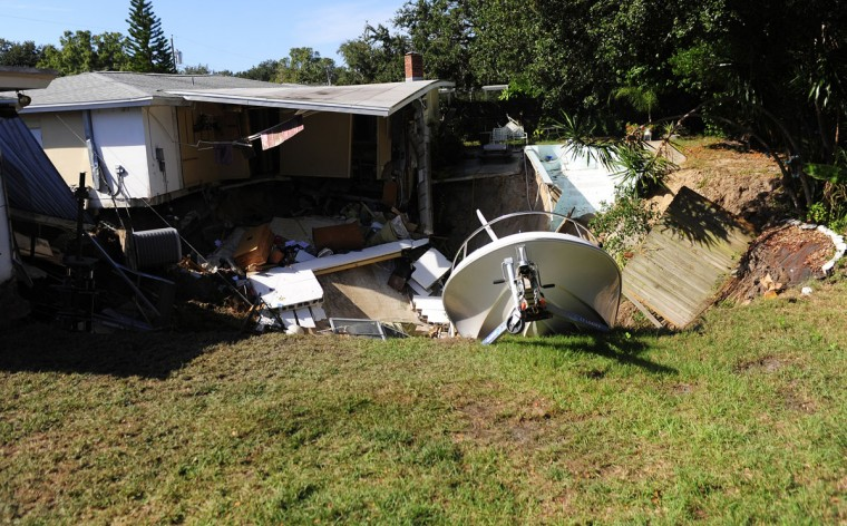 The rear portion of a residential home is consumed by a sinkhole November 14, 2013 in Dunedin, Florida. According to reports, the large sinkhole began to form between two houses the morning of November 14, and has grown to size of about 30 feet wide by 30 feet deep. (Pool Photo by Luke Johnson-Pool/Getty Images)