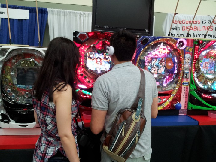 A couple tries their hand at the authentic Japanese pachinko machines in the game room at Otakon. (Carrie Wood/For the Darkroom)