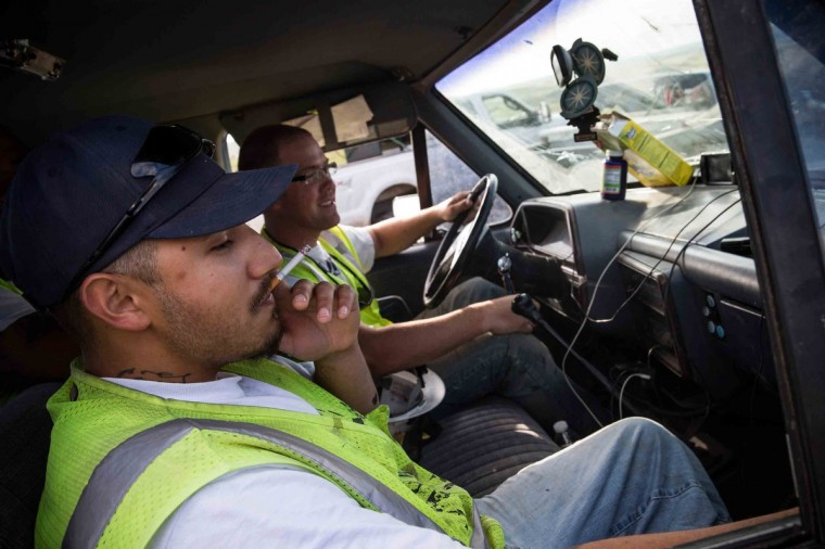 A construction worker smokes a cigarette and watches television on an iPhone while waiting for the day's orders on July 25, 2013 outside Watford City, North Dakota. North. (Andrew Burton/Getty Images)