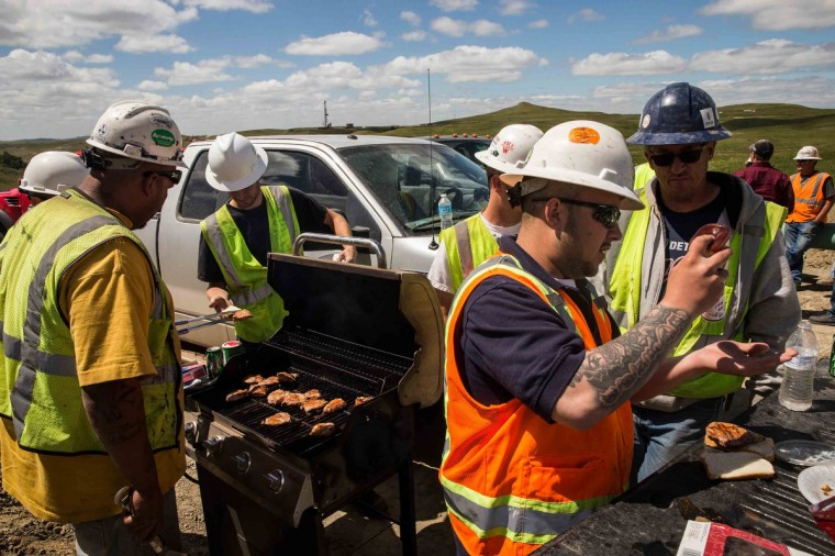 Construction workers specializing in pipe-laying grill lunch while working on a pipeline that will stream line oil production from drill sites to train yards and oil refineries on July 25, 2013 outside Watford City, North Dakota. (Andrew Burton/Getty Images)
