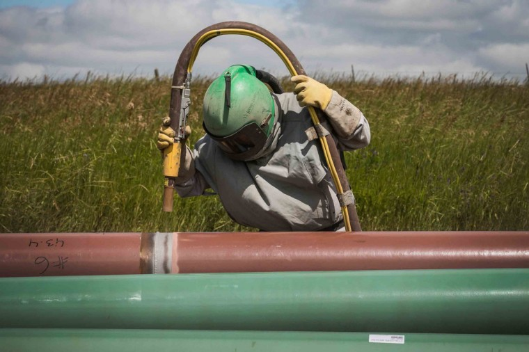 A construction worker specializing in pipe-laying sandblasts a section of pipeline on July 25, 2013 outside Watford City, North Dakota. Pipelines are being constructed across the state in part to streamline the movement of oil from drill sites to train depots and oil refineries. (Andrew Burton/Getty Images)