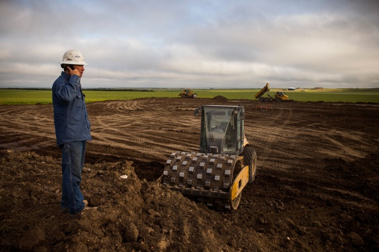A foreman with JMac Resources reviews a site being cleared for construction in the middle of a canola field on July 26, 2013 outside Williston, North Dakota. (Andrew Burton/Getty Images)