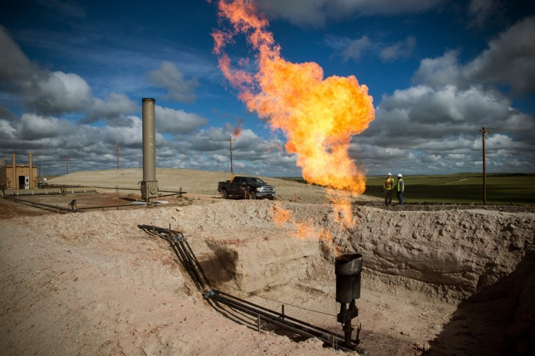 A gas flare is seen at an oil well site on July 26, 2013 outside Williston, North Dakota. Gas flares are created when excess flammable gases are released by pressure release valves during the drilling for oil and natural gas. (Andrew Burton/Getty Images)
