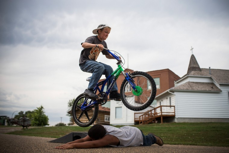 Fielding (on bike), jumps over Zach on July 28, 2013 in Alexander, North Dakota. Fielding's dad, who works as a mechanic and welder, moved the family to North Dakota from Mexico after learning of work being offered. (Andrew Burton/Getty Images)