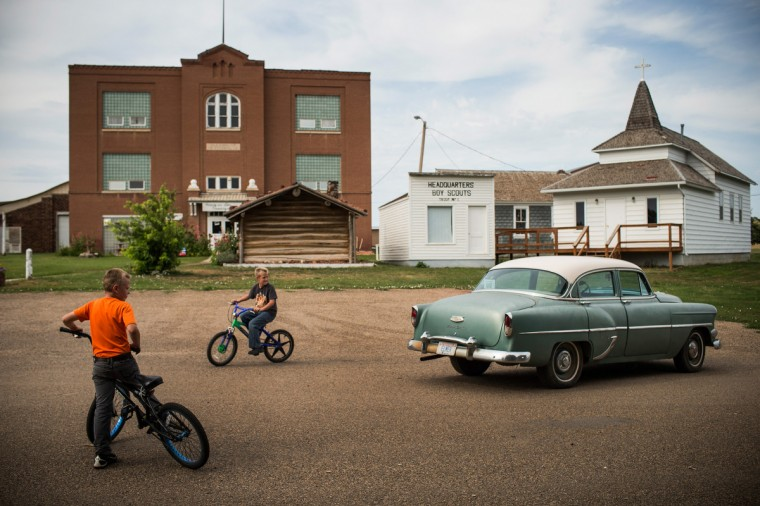 Fielding (R), and Jerome (L) ride their bikes on July 28, 2013 in Alexander, North Dakota. Fielding's dad, who works as a mechanic and welder, moved the family to North Dakota from Mexico after learning of work being offered. (Andrew Burton/Getty Images)