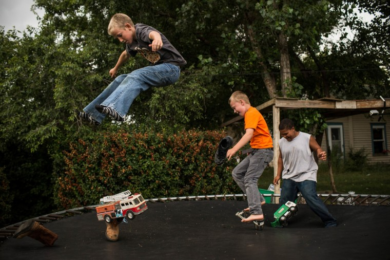 Fielding (L), Jerome (C) and Zach bounce on a trampoline on July 28, 2013 in Alexander, North Dakota. Fielding's dad, who works as a mechanic and welder, moved the family to North Dakota from Mexico after learning of work being offered. (Andrew Burton/Getty Images)