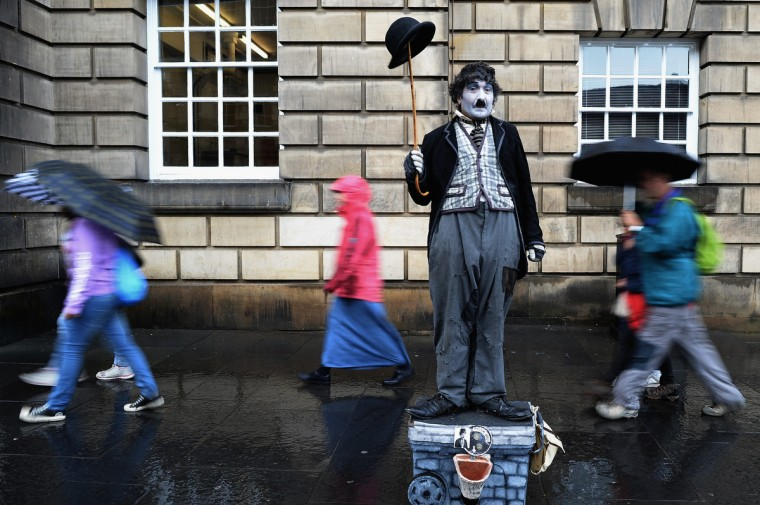 Members of the public, walk past a street entertainer on the Royal Mile on July 29, 2013 in Edinburgh, Scotland. The city is preparing ahead of the Edinburgh Fringe Festival which runs from the 2 -26 August and is one of the largest arts festivals in the world, dating back to 1947. The festival attracts thousands of performers from across the world to showcase their acts in Scotland's capital. (Jeff J Mitchell/Getty Images)