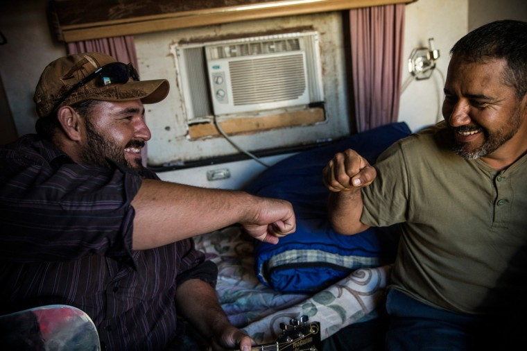 Ramone Garcia (L) and his brother Samuel Garcia play music in their trailer on July 29, 2013 in Watford City, North Dakota. The Garcia brothers live in the trailer with their two other brothers and all work in the oil industry; prior to moving the North Dakota a year ago, they lived in Arizona, where their wives and children still reside. North Dakota has seen an influx of workers come from around the globe as a new oil boom has begun. (Andrew Burton/Getty Images)