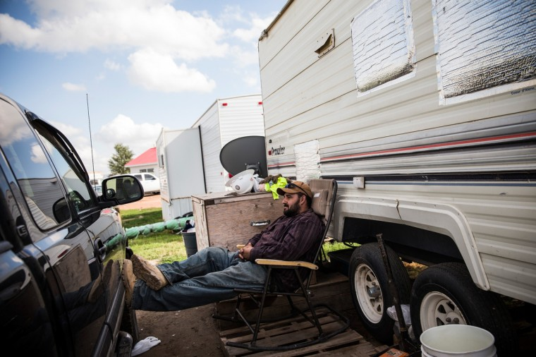 Ramone Garcia waits for his brother to get home to unlock their trailer on July 29, 2013 in Watford City, North Dakota. Garcia lives in the trailer with his three other brothers - they all work in the oil industry; prior to moving the North Dakota a year ago, they lived in Arizona, where their wives and children still reside. The trailer has no running water, and bathrooms are found in a communal building nearby. (Andrew Burton/Getty Images)