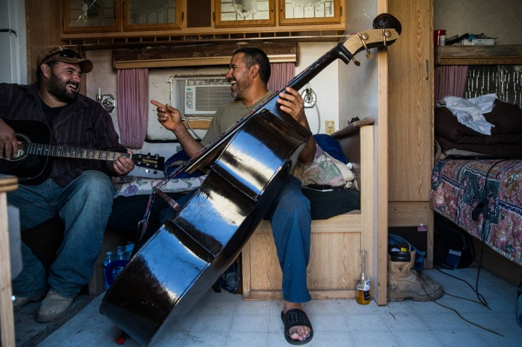 Ramone Garcia (L) and his brother Samuel Garcia play music in their trailer on July 29, 2013 in Watford City, North Dakota. (Andrew Burton/Getty Images)
