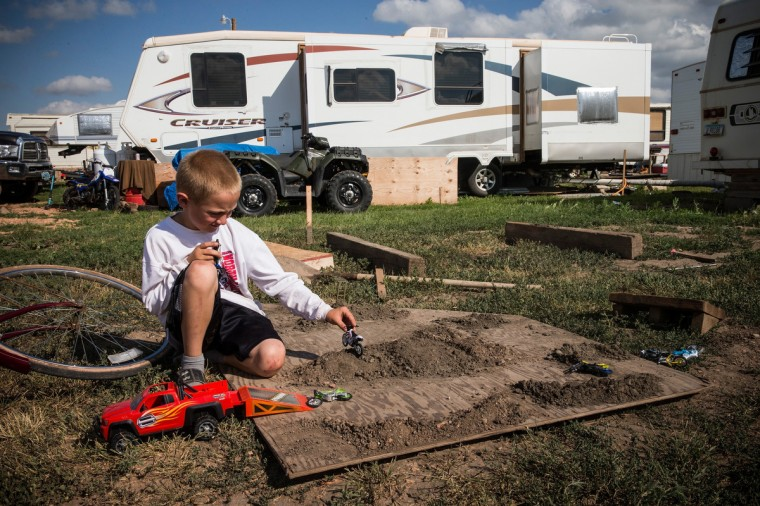 A boy plays with toy motorcycles in a trailer park on July 29, 2013 in Watford City, North Dakota. The trailer park is intended for oil workers traveling to the state. It has no running water, and bathrooms are found in a communal building nearby. North Dakota has seen an influx of workers come from around the globe as a new oil boom has begun. (Andrew Burton/Getty Images)