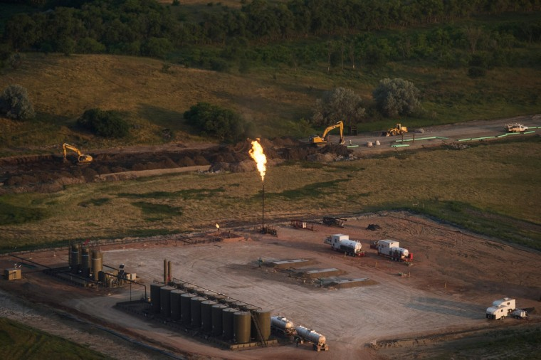 A gas flare is seen in an aerial view in the early morning hours of July 30, 2013 near Watford City, North Dakota. Gas flares are caused when pressure release valves release excess natural gas from an oil pumpjack; the gas is then ignited to burn off the fumes. (Andrew Burton/Getty Images)