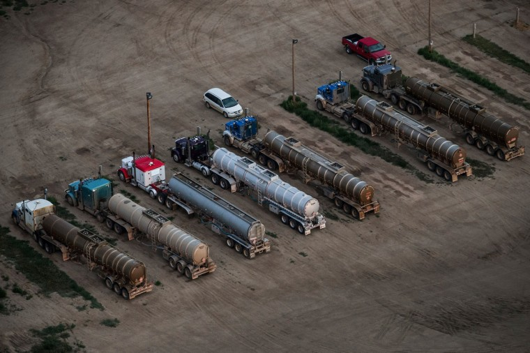 Tractor trailers at a salt-water treatment plant are seen in an aerial view in the early morning hours of July 30, 2013 near Watford City, North Dakota. (Andrew Burton/Getty Images)