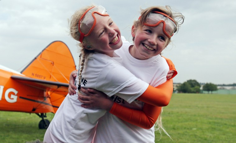 Nine-year-old cousins Rose Brewer (L) and Flame Brewer (R) hug each other after they completed their wingwalk over Rendcomb airfield in Gloucestershire, to become the world's youngest formation wingwalkers in Cirencester, England. (Matt Cardy/Getty Images)