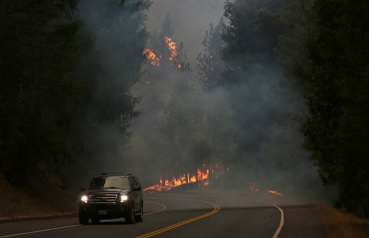 A car drives along US highway 120 as the Rim Fire burns out of control on August 21, 2013 in Buck Meadows, California. The Rim Fire continues to burn out of control and threatens 2,500 homes outside of Yosemite National Park. Over 400 firefighters are battling the blaze that is only 5 percent contained. (Justin Sullivan/Getty Images)