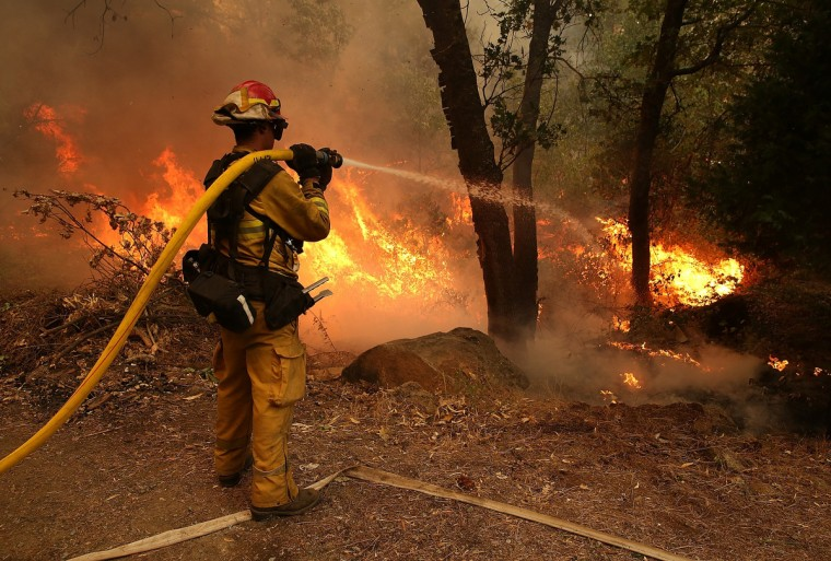 A firefighter from Ebbetts Pass Fire District uses a hose to cool down hot spots of back fire as he battles the Rim Fire on August 21, 2013 in Groveland, California. The Rim Fire continues to burn out of control and threatens 2,500 homes outside of Yosemite National Park. Over 400 firefighters are battling the blaze that is only 5 percent contained. (Justin Sullivan/Getty Images)