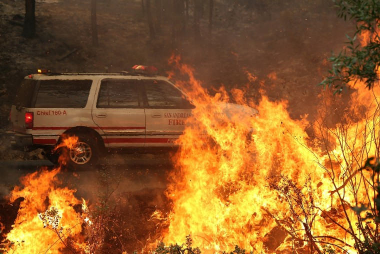A vehicle from San Andreas fire department drives by a back fire as crews battle the Rim Fire on August 21, 2013 in Groveland, California. The Rim Fire continues to burn out of control and threatens 2,500 homes outside of Yosemite National Park. Over 400 firefighters are battling the blaze that is only 5 percent contained. (Justin Sullivan/Getty Images)