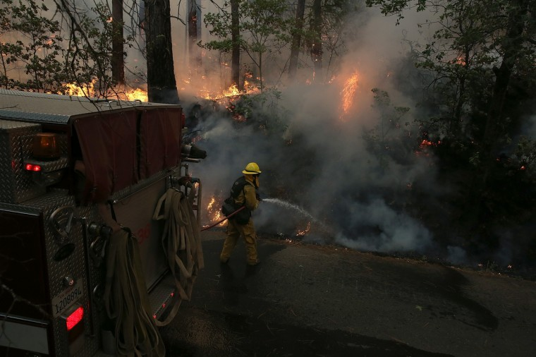 A firefighter from Ebbetts Pass Fire District uses a hose to cool down hot spots of back fire while battling the Rim Fire on August 21, 2013 in Groveland, California. The Rim Fire continues to burn out of control and threatens 2,500 homes outside of Yosemite National Park. Over 400 firefighters are battling the blaze that is only 5 percent contained. (Justin Sullivan/Getty Images)