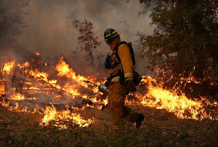 A firefighter from Ebbetts Pass Fire District uses a drip torch to light a back fire while battling the Rim Fire on August 21, 2013 in Groveland, California. The Rim Fire continues to burn out of control and threatens 2,500 homes outside of Yosemite National Park. Over 400 firefighters are battling the blaze that is only 5 percent contained. (Justin Sullivan/Getty Images)