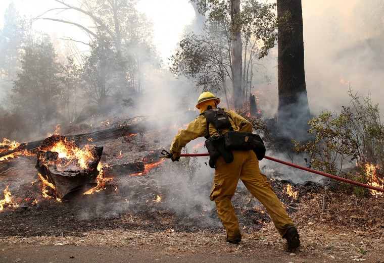 A firefighter from Ebbetts Pass Fire District uses a hose to cool down hot spots while battling the Rim Fire on August 21, 2013 in Groveland, California. The Rim Fire continues to burn out of control and threatens 2,500 homes outside of Yosemite National Park. Over 400 firefighters are battling the blaze that is only 5 percent contained. (Justin Sullivan/Getty Images)