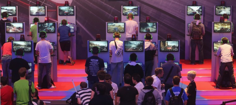 Gaming enthusiasts try out the 'Need for Speed Rivals' game on the new XBOX at the Gamescom 2013. (Juergen Schwarz/Getty Images)