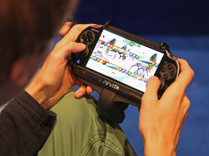 A gaming enthusiast tries out a Sony Playstation Vita game at the Gamescom 2013 gaming trade. (Juergen Schwarz/Getty Images)