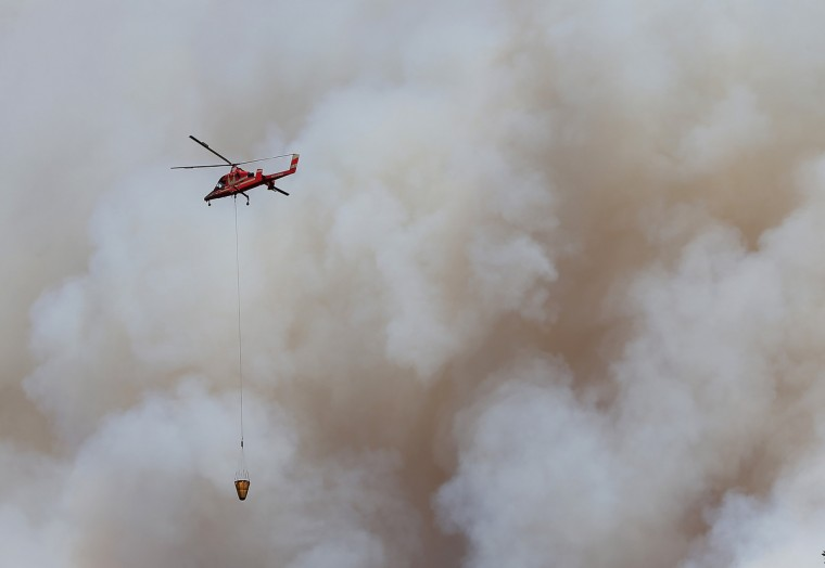 A firefighting helicopter flies in front of a plume of smoke from the Rim Fire on August 22, 2013 in Groveland, California. The Rim Fire continues to burn out of control and threatens 2,500 homes outside of Yosemite National Park. Over 1,000 firefighters are battling the blaze that was reduced to only 2 percent containment after it nearly tripled in size overnight. (Justin Sullivan/Getty Images)