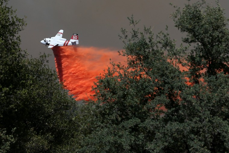 A California Department of Forestry air tanker drops fire retardant on a ridge ahead of the advancing Rim Fire on August 22, 2013 in Groveland, California. The Rim Fire continues to burn out of control and threatens 2,500 homes outside of Yosemite National Park. (Justin Sullivan/Getty Images)