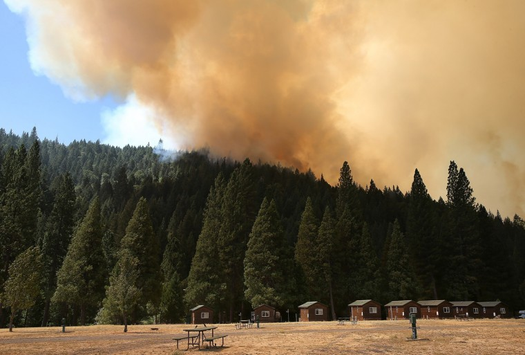 A plume of smoke rises from a ridge as the Rim Fire approaches Yosemite Lakes on August 23, 2013 near Groveland, California. The Rim Fire continues to burn out of control and threatens 4,500 homes outside of Yosemite National Park. (Justin Sullivan/Getty Images)