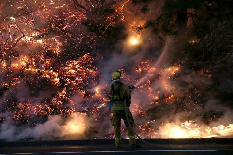 A firefighter uses a hose to douse the flames of the Rim Fire on August 24, 2013 near Groveland, California. The Rim Fire continues to burn out of control and threatens 4,500 homes outside of Yosemite National Park. Over 2,000 firefighters are battling the blaze that has entered a section of Yosemite National Park and is currently 5 percent contained. (Justin Sullivan/Getty Images)