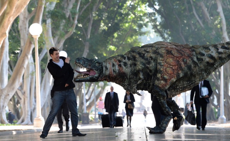 "A Tyrannosaurus rex takes a morning stroll with commuters in Hyde Park in Sydney, Australia. In a world first, the Australian Museum presents ""Tyrannosaurs: Meet the Family"", an innovative, multimedia experience showcasing the newly-revised tyrannosaur family tree. With over 10 life-sized dinosaur specimens on display, including one of the oldest tyrannosaurs, Guanlong wucaii, the exhibition runs from 23 November 2013 to 27 July 2014. Showcasing a dramatic array of fossils and casts of tyrannosaur specimens, including never before-seen specimens from China, ""Tyrannosaurs: Meet the Family"" is designed to provide a snapshot of dinosaur life and show how this group became the world's top predators with their massive skulls, powerful jaws and bone-crunching teeth. (James Morgan/Destination New South Wales via Getty Images)"